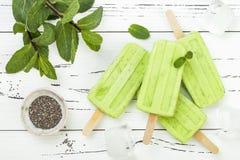Domowej roboty weganin zielonej herbaty matcha mennicy kokosowego mleka popsicles z chia ziarnami na nieociosanym białym drewnian Zdjęcia Stock