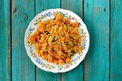 Domowej roboty weganinu dyniowy pilaf w kolorowym talerzu na turkusowym tabl Zdjęcia Royalty Free