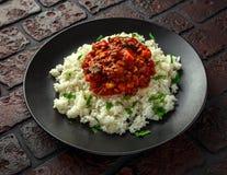 Domowej roboty wołowina mince i jarzynowa potrawka słuzyć z ryż na czarnym talerzu fotografia stock