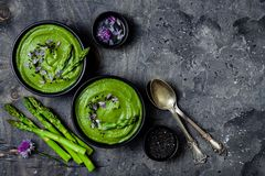 Domowej roboty zielonej wiosny szparagowa kremowa polewka dekorująca z czarnymi sezamowymi ziarnami i jadalnymi szczypiorków kwia Fotografia Royalty Free