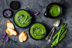 Domowej roboty zielonej wiosny szparagowa kremowa polewka dekorująca z czarnymi sezamowymi ziarnami i jadalnymi szczypiorków kwia Zdjęcie Royalty Free
