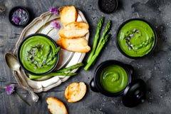 Domowej roboty zielonej wiosny szparagowa kremowa polewka dekorująca z czarnymi sezamowymi ziarnami i jadalnymi szczypiorków kwia Obraz Stock