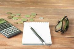 Domowi savings, budżeta pojęcie Wzorcowy dom, notepad, pióro, kalkulator i monety na drewnianym biurowego biurka stole, Fotografia Stock