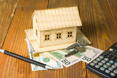 Domowi savings, budżeta pojęcie Wzorcowy dom, pióro, kalkulator i monety na drewnianym biurowego biurka stole, Zdjęcie Stock