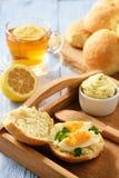 Domowy śniadanie domowej roboty chlebowe rolki, filiżanka herbata, gotowani jajka i czosnku zielarski masło -, Obraz Royalty Free