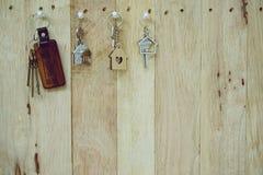Domowy klucz z drewnianym domowym keyring obwieszeniem na drewno deski tle, majątkowy pojęcie, kopii przestrzeń obrazy stock