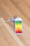 Domowy klucz z energetyczną etykietką na drewnie Zdjęcia Royalty Free
