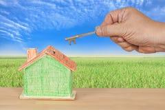 Domowy klucz z miniaturowym modela domem na krajobrazie Obraz Royalty Free