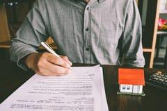Domowy kontrakt, mężczyzna podpisuje kontrakt nabywać dom z r obrazy royalty free