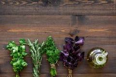 Domowy kucharstwo z świeżym greenery i organicznie olejem na drewnianym stołowym tło odgórnego widoku egzaminie próbnym up obrazy stock