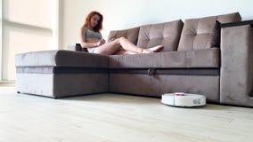 domowy m?drze Czyścić domu mechaniczny próżniowy czystego, gdy kobiety opierać się na kanapach bawić się telefony komórkowych zbiory