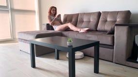 domowy m?drze Czyścić domu mechaniczny próżniowy czystego, gdy kobiety opierać się na kanapach bawić się telefony komórkowych zdjęcie wideo