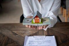 Domowy model i pieniądze w ręce zdjęcie royalty free