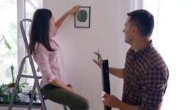 Domowy odświeżanie, szczęśliwi nowożeńcy wiesza obraz i półka na ścianie i dziewczynie całuje samiec w mieszkaniu zdjęcie wideo