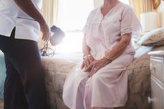 Domowy opiekun z starszym kobiety obsiadaniem na łóżku zdjęcia royalty free