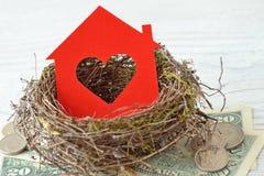 Domowy papier z sercem w gniazdeczku na pieniądze tle - miłość dla domu, domowy asekuracyjny pojęcie zdjęcie royalty free