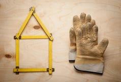 Domowy pojęcie z żółtym metrem i pracującymi rękawiczkami Obrazy Stock