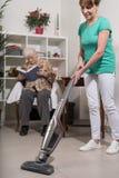Domowy pomagier vacuuming dla starej kobiety fotografia royalty free