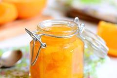 Domowy pomarańczowy dżem Słodki pomarańczowy dżem w szklanym słoju, łyżka, tkanina, pielucha, pomarańcze plasterki na stole Łatwy Obrazy Royalty Free