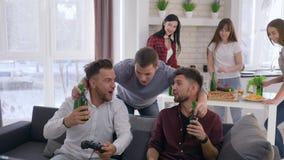 Domowy przyjęcie, gamers przyjaciół faceci bawić się gra wideo i napoju piwo podczas gdy dziewczyny w tle przygotowywają przekąsk zbiory