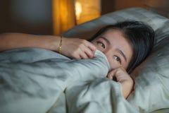 Domowy styl życia portret młoda piękna smutna i przygnębiona Azjatycka Chińska kobieta obudzona w łóżkowym nocnym cierpienie niep obraz stock