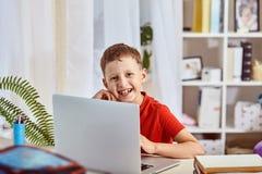 Domowy uczyć kogoś, rewizja i nauka, nowa wiedza szczęśliwy dziecko przy stołem z komputerem chłopiec studencki obsiadanie przy s obrazy royalty free