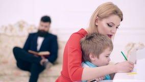 Domowy uczy kogo? poj?cie Ojcuje czytelnicz? ksi??k?, luksusowy wn?trze podczas gdy matka uczy syna preschooler rysowa? lub pisa? zdjęcie wideo
