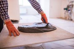 Domowy ulepszenie, odświeżanie - pracownika budowlanego kaflarz tafluje, ceramiczna dachówkowa podłoga adhezyjna zdjęcie stock