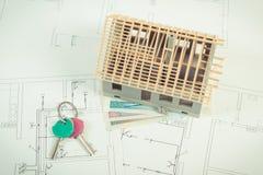 Domowy w budowie, poleruje waluta klucze na elektrycznych rysunkach, pieniądze i diagramy dla projekta i, buduje do domu kosztu c Zdjęcia Royalty Free
