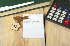 Domowych savings, budżeta, pieniężnego i majątkowego pojęcie, Wzorcowy dom, klucze, kalkulator i notepad z tekstem REAL ESTATE da Zdjęcia Royalty Free