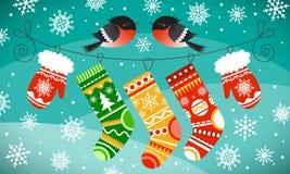 Dompfaffe auf der Linie mit Weihnachtshandschuhen und -socken Schneeflocken und schneebedeckter Hügelhintergrund Lizenzfreie Stockfotografie