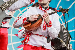 Domra player in traditional Russian clothes. Close up musician playing domra on a Russian fair festival Stock Photo