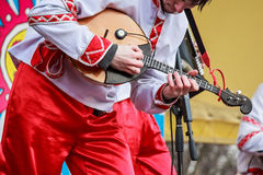 Domra player in traditional Russian clothes. Close up musician playing domra on a Russian fair festival Stock Photography