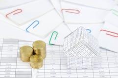 Domu i kroka złociste monety papierkową robotę z kolorowym paperclip Zdjęcia Royalty Free