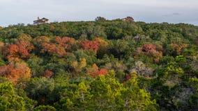 Domy na górze lasowego wzgórza z spadkiem barwili drzewa fotografia stock