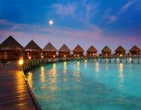 Domy na stosach na wodzie przy nocą w dureń księżyc świetle. Noc tropikalny krajobraz Fotografia Stock