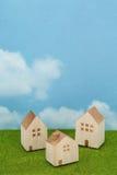 Domy na zielonej trawie nad niebieskim niebem i chmurami Zdjęcie Royalty Free