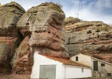 Domy przy bazą czerwonego piaskowa monolity w Chequilla wiosce, prowincja Guadalajara, Hiszpania zdjęcie stock