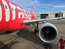 Jet engine generate thrust under the wing of Thai Airasia, Airbus A320 airplane parked on the parking lot with ground staff. royalty free stock photos