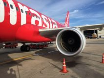 Jet engine generate thrust under the wing of Thai Airasia, Airbus A320 airplane parked on the parking lot. royalty free stock images