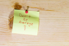 Don't be average. Written in red ink on yellow post it note tacked to wood stock images