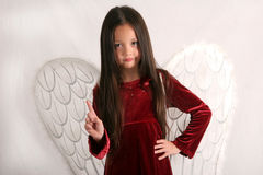 Don't be naughty. Young girl dressed in angel wings waving her finger in warning or disapproval Stock Image