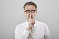 Don't be so noisy, please. Man makes gesture with his finger to be silent stock photos