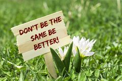 Don`t be the same be better. On wooden sign in garden with white spring flower Stock Photo
