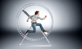 Don `t be a slave. Man running in huge hamster wheele royalty free stock photo