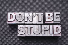 Don't be stupid bm. Don't be stupid phrase made from metallic letterpress blocks on black perforated surface royalty free stock photo