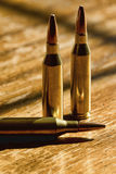 Don't Bite The Bullet. These are 243 rifle cartridges on a wood table in the sunshine royalty free stock images