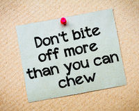 Don't bite off more than you can chew. Message. Recycled paper note pinned on cork board. Concept Image Stock Photo