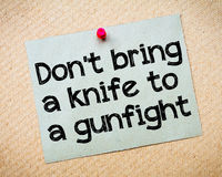 Don't bring a knife to a gunfight Royalty Free Stock Image