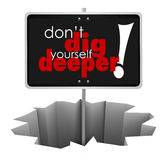 Don't Dig Yourself Deeper Sign Deeper SIgn in Hole. Don't Dig Yourself Deeper words on sign in a hole to illustrate advice or wisdom encouraging you to solve a Royalty Free Stock Photo